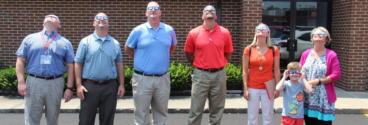 Administrators using eclipse glasses.