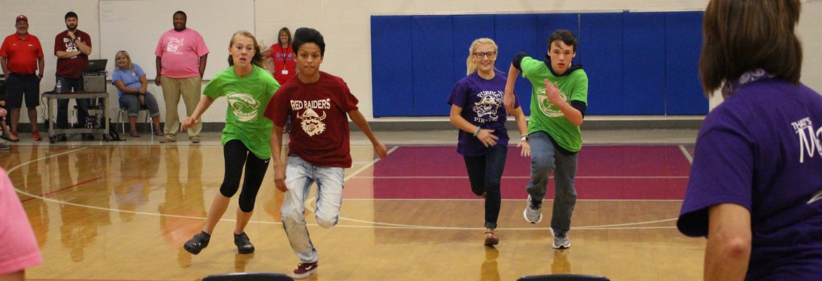 Students Carson McReynolds (8), Angel Damian(7), KayBreona Gamble (7), & Nathaniel Toon (8) race to see who can reach the chairs at the finish line first.  The race was part of the first annual Crew day festivities.