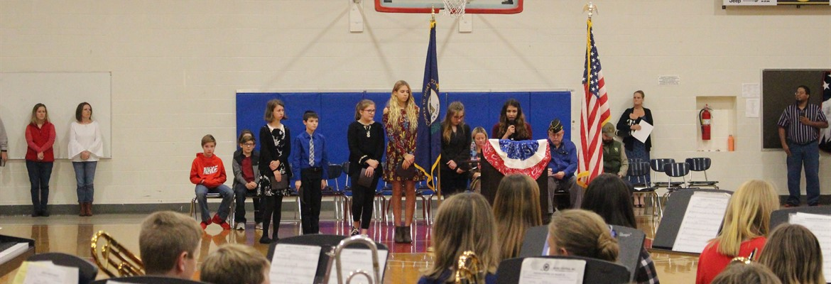 Speech team members participate in the annual Veteran's Day assembly.  Each member shown told history that related to the armed services and the history of Veteran's Day.
