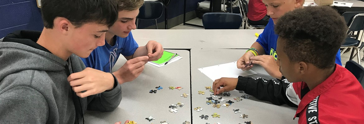 Eighth grade students in Mrs. Roach's science class work together to complete a jigsaw puzzle.