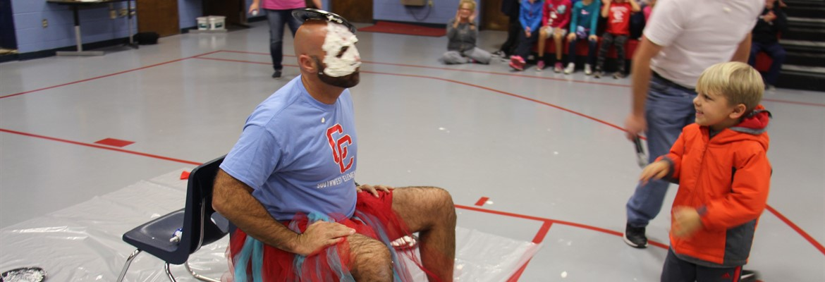 Mr. McKeel was pied in the face and wore a tutu due to the students meeting his challenge of bringing in over 4,000 cans of sweet peas for Needline.  The final can total was 6,438.